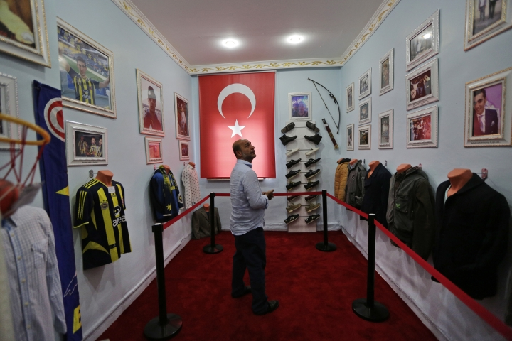 In this Thursday, July 6, 2017 photo, Tarkan Ecebalin walks in his late son Tolga's former home in Istanbul. The father turned the modest house into a museum honouring his child, who was 27 when he was killed during the July 15, 2016 failed military coup. (AP Photo/Lefteris Pitarakis)