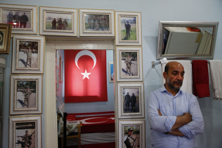 In this Thursday, July 6, 2017 photo, Tarkan Ecebalin stands in his late son Tolga's former home in Istanbul. The father turned the modest house into a museum honouring his child, who was 27 when he was killed during the July 15, 2016 failed military coup. (AP Photo/Lefteris Pitarakis)