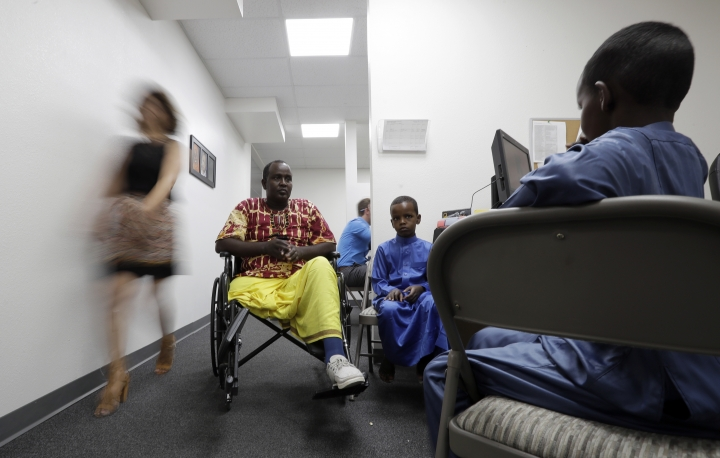 FILE - In this July 6, 2017, file photo, Ali Said, of Somalia, center, waits at a center for refugees with his two sons in San Diego. Said, whose leg was blown off by a grenade, says he feels unbelievably lucky to be among one of the last refugees allowed into the United States before stricter rules were to kick in as part of the Trump administration's proposed travel ban. A federal judge in Hawaii further weakened the already-diluted travel ban Thursday, July 13, 2017, by vastly expanding the list of U.S. family relationships that visitors from six Muslim-majority countries can use to get into the country. (AP Photo/Gregory Bull, File)