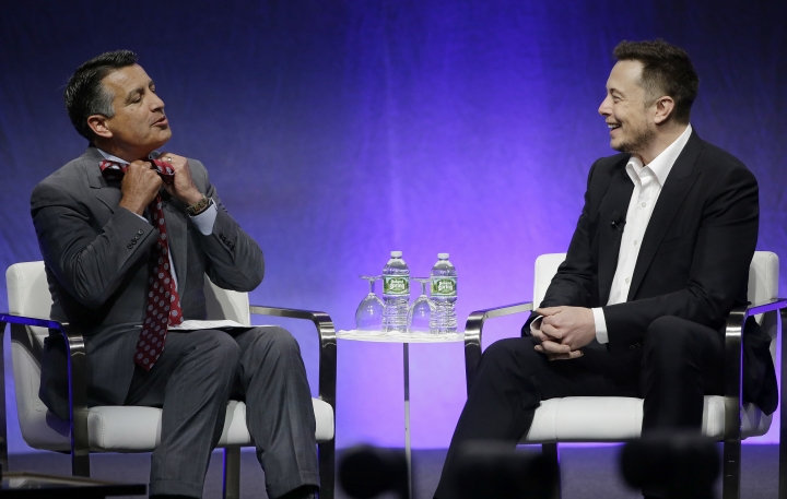 """Nevada Republican Gov. Brian Sandoval takes off his tie as he tells Tesla and SpaceX CEO Elon Musk he planned to take it off when Musk was introduced during the closing plenary session entitled """"Introducing the New Chairs Initiative - Ahead"""" on the third day of the National Governors Association's meeting Saturday, July 15, 2017, in Providence, R.I. Musk, in a suit, is not wearing a tie. (AP Photo/Stephan Savoia)"""