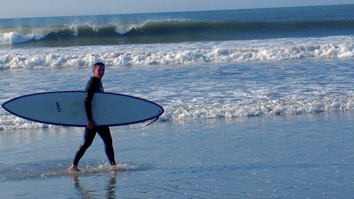 In this August 2010 photo provided by Harry Martin, then-U.S. Army Gen. Michael Flynn carries his surfboard on Sachuest Beach, in Middletown, R.I. The former National Security Adviser, at the center of multiple probes into Russia's interference in the 2016 presidential election, is seeking sanctuary from the swirling eddy of news coverage in the beach town where he grew up. (Harry Martin via AP)