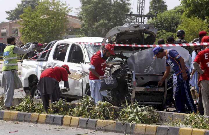 Pakistani security officers and volunteers collect evidence at the site of a bombing in Peshawar, Pakistan, Monday, July 17, 2017. A suicide bomber hit a vehicle carrying Pakistani paramilitary force members on Monday, killing soldiers, including an officer, and wounding seven, a police official said. The Taliban quickly claimed responsibility for the attack. (AP Photo/Muhammad Sajjad)