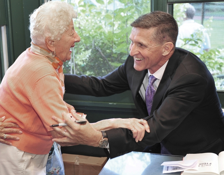 In this Aug. 22, 2016, photo, retired Lt. Gen. Michael Flynn, right, greets family friend Dee Potter, of Middletown, R.I., at a restaurant in Newport, R.I. The former National Security Adviser, at the center of multiple probes into Russia's interference in the 2016 presidential election, is seeking sanctuary from the swirling eddy of news coverage in Middletown, R.I., the beach town where he grew up. (Dave Hansen/TheNewport Daily News via AP)
