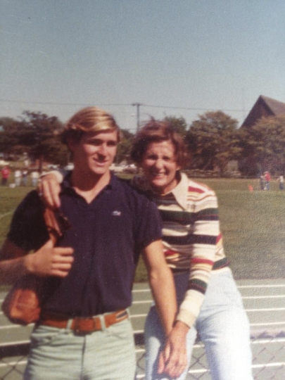 In this photo, date unknown, provided by Joe Flynn, Michael Flynn, left, stands with his mother Helen Flynn, right, near a football field, in Middletown, R.I. The former National Security Adviser, at the center of multiple probes into Russia's interference in the 2016 presidential election, is seeking sanctuary from the swirling eddy of news coverage in Middletown, R.I., the beach town where he grew up. (Charlie Flynn via AP)