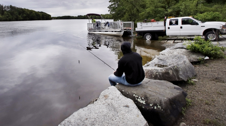 """In this Wednesday June 7, 2017 photo, Kevin Garcia fishes along the banks of the Merrimack River as a """"Clean River Project"""" recovery boat is offloaded in Chelmsford, Mass. Syringes left by drug users amid the heroin crisis are turning up everywhere. They hide in weeds along hiking trails and in playground grass, get washed into rivers and onto beaches, and lie scattered about in baseball dugouts and on sidewalks and streets. There are reports of children finding them and getting poked. (AP Photo/Charles Krupa)"""