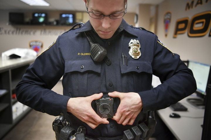 In this Feb. 16, 2017 photo, Maplewood Police Officer Parker Olding attaches his body camera to the magnetic plate worn inside his uniform in Maplewood, Minn. When a Minneapolis police officer shot and killed Justine Damond, who had called in a possible crime in the alley behind her house on July 15, his body camera wasn't running. Criminal-justice experts say the early numbers suggest that officers aren't turning them on often enough, and Minneapolis isn't the only city where that's the case. (Glen Stubbe/Star Tribune via AP)