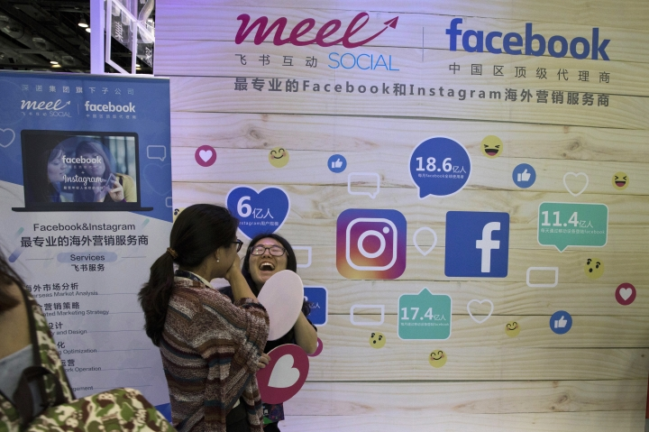 In this Friday, April 28, 2017, photo, a woman reacts near a booth promoting overseas marketing services on Facebook and instagram which are banned in China during an internet conference in Beijing. China is clamping down on use of virtual private networks, or VPNs, in a move that foreign companies worry might disrupt their operations or jeopardize trade secrets. (AP Photo/Ng Han Guan)