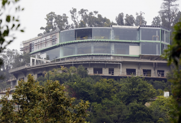FILE - This May 31, 2017 file photo shows a huge mansion under construction on Strada Vecchia Road in the Bel Air district of Los Angeles. Mohamed Hadid, the father of fashion models Bella and Gigi Hadid, has been fined and given community service for illegally building the gigantic mansion in Los Angeles' Bel Air district. The Los Angeles Times reports that Hadid was sentenced Thursday, July 20, 2017, to 200 hours of service, fined $3,000 and ordered pay the city more than $14,000 to cover building department costs. (AP Photo/Damian Dovarganes, File)