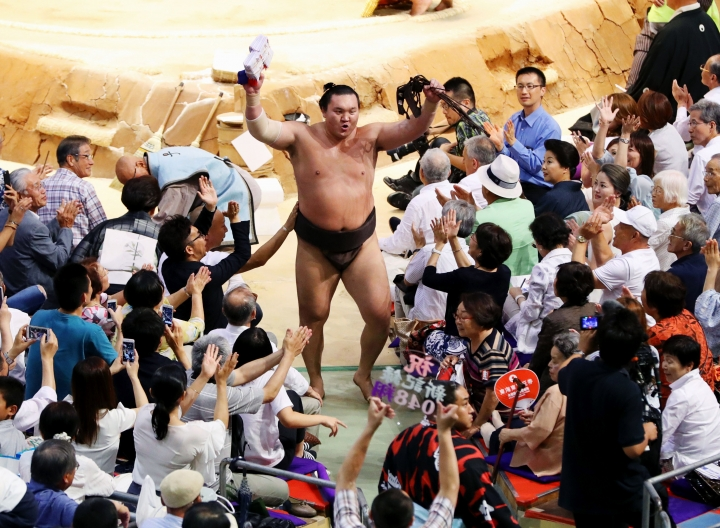 Mongolian grand champion Hakuho is cheered by spectators as he leaves the ring after beating champion Takayasu in their bout during the Nagoya Grand Sumo Tournament in Nagoya, central Japan, Friday, July 21, 2017. Hakuho set a record of 1,048 carrier match wins in sumo history. (Meika Fujio/Kyodo News)