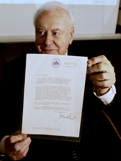 FILE - In this November 7, 2005 file photo, former Australian Prime Minister Gough Whitlam holds up the original copy of his dismissal letter he received from then Governor General Sir John Kerr on the 11th of November 1975 at a book launch in Sydney, Australia. Historian, Professor Jenny Hocking, is going to court in July, 2017 in an attempt to force Australian authorities to release secret letters that would reveal what Queen Elizabeth II knew of her representative's shocking scheme to dismiss Australia's government more than 40 years ago. (AP Photo/Mark Baker, File)