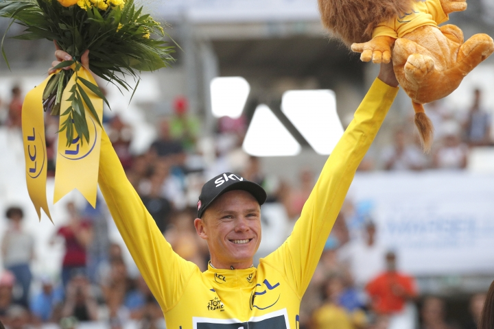 Britain's Chris Froome, wearing the overall leader's yellow jersey, celebrates on the podium after the twentieth stage of the Tour de France cycling race, an individual time trial over 22.5 kilometers (14 miles) with start and finish in Marseille, southern France, Saturday, July 22, 2017. (AP Photo/Christophe Ena)