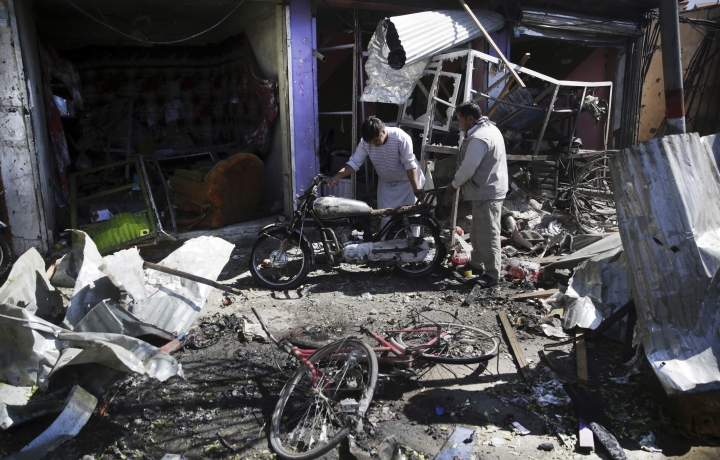 Men look at the remains of their properties at the site of a suicide attack in Kabul, Afghanistan, Monday, July 24, 2017. A suicide car bomb killed dozens of people as well as the bomber early Monday morning in a western neighborhood of Afghanistan's capital where several prominent politicians reside, a government official said. (AP Photos/Massoud Hossaini)