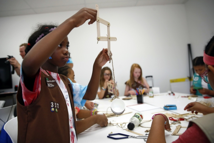 In this July 21, 2017 photo, Cayla Hicks, 7, a member of the Girl Scouts of Central Maryland, creates a simple robotic arm out of wooden sticks, fasteners and rope during an activity introducing the world of robotics in Owings Mills, Md. Girl Scouts of all ages can now earn 23 new badges focused on science, technology, engineering and math, the largest addition of new badges in a decade. The effort takes a progressive approach to STEM and also nudges girls to become citizen scientists using the great outdoors as their laboratory. (AP Photo/Patrick Semansky)
