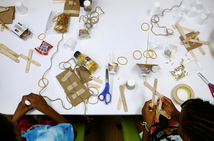 In this July 21, 2017 photo, members of the Girl Scouts of Central Maryland use various materials to build simple robotic arms as they participate in an activity introducing them to the world of robotics in Owings Mills, Md. The Girl Scouts of the USA is unveiling a major push this week into furthering the interest of girls in science, engineering, technology and math through 23 new badges, its largest addition of new badges in a decade. (AP Photo/Patrick Semansky)