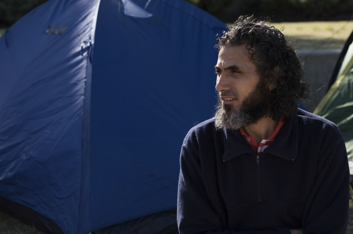 FILE - In this May 5, 2015 file photo, Abu Wa'el Dhiab, from Syria, sits in front of the U.S. embassy while visiting former fellow detainees demanding financial assistance from the U.S., in Montevideo, Uruguay. Authorities reported on Monday, July 24, 2017, that Dhiab has returned to Uruguay after being deported from Morocco. (AP Photo/Matilde Campodonico, File)