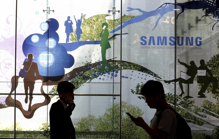 In this Wednesday, July 26, 2017 photo, people pass by Samsung Electronics shop in Seoul, South Korea. Samsung Electronics on Thursday, July 27, said its second-quarter profit surged 85 percent to record high thanks to memory chips. (AP Photo/Ahn Young-joon)