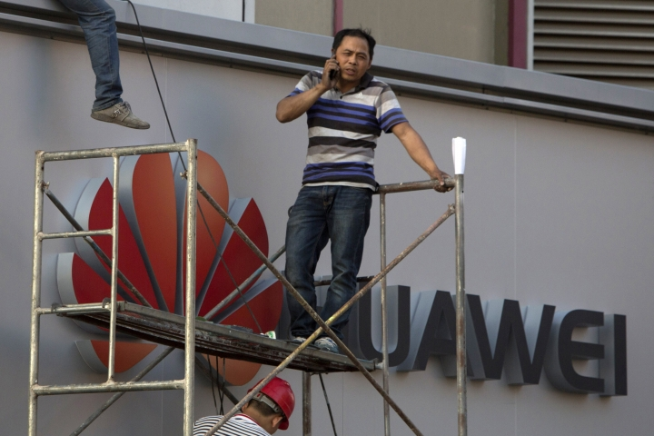 In this May 31, 2017, photo, a worker talks on his phone near the logo for Huawei in Beijing. China's Huawei Technology says Thursday, July 2017 that first-half revenues at its telecom equipment and smartphone businesses expanded at a slower pace than the year before. (AP Photo/Ng Han Guan)