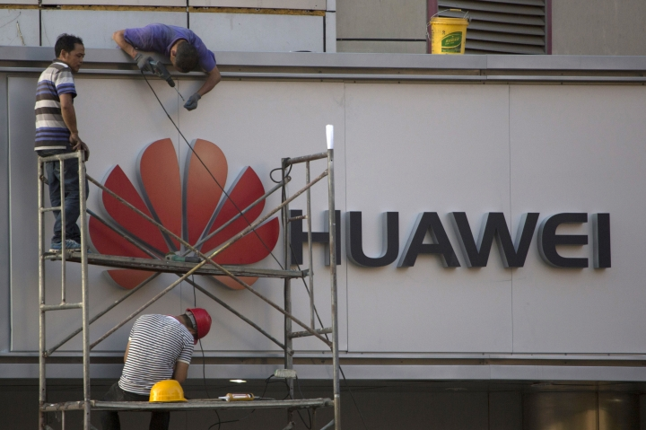 In this May 31, 2017, photo, workers fix panels near the logo for Huawei in Beijing. China's Huawei Technology said Thursday, July 2017 that first-half revenues at its telecom equipment and smartphone businesses expanded at a slower pace than the year before. (AP Photo/Ng Han Guan)