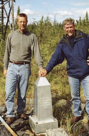In this undated photo provided by Brian Butler, Butler of Holliston, Mass., left, and his brother Gregg stand at the monument marking the spot where Saskatchewan, Manitoba, the Northwest Territories and Nunavut meet. Such remote corners have become destinations for adventurist tourists such as Brian. (Courtesy of Brian Butler via AP)
