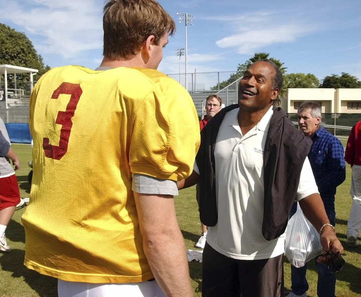 FILE - In this Dec. 28, 2002, file photo, University of Southern California quarterback Carson Palmer talks to O.J. Simpson after practice for the Orange Bowl in Davie, Fla. The two are winners of the Heisman trophy. USC head coach Todd Helton told reporters on July 27, 2017, that Simpson wouldn't be invited to watch practice or take part in any official functions at his alma mater this fall following his release from prison. (AP Photo/J. Pat Carter, File)