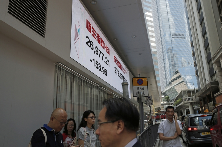 People walk past an electronic stock board showing the Hang Seng Index at a bank in Hong Kong, Friday, July 28, 2017. Asian shares slid Friday as investors evaluated the latest raft of corporate earnings, including those from tech stocks, which had a poor day on Wall Street and weighed on overall investor sentiment. (AP Photo/Kin Cheung)