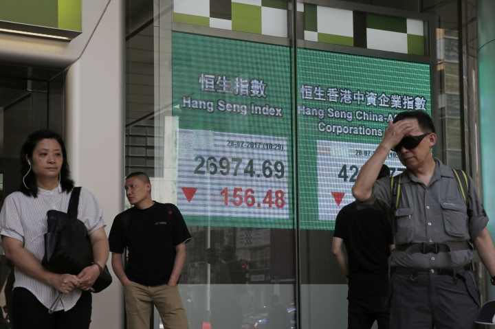 People stand in front of an electronic stock board showing the Hang Seng Index at a bank in Hong Kong, Friday, July 28, 2017. Asian shares slid Friday as investors evaluated the latest raft of corporate earnings, including those from tech stocks, which had a poor day on Wall Street and weighed on overall investor sentiment. (AP Photo/Kin Cheung)