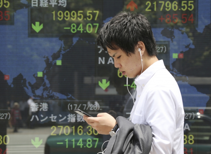 A man walks by an electronic stock board of a securities firm in Tokyo, Friday, July 28, 2017. Asian shares slid Friday as investors evaluated the latest raft of corporate earnings, including those from tech stocks, which had a poor day on Wall Street and weighed on overall investor sentiment. (AP Photo/Koji Sasahara)