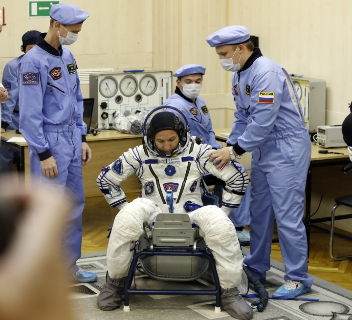 Russian Space Agency experts help to U.S. astronaut Randy Bresnik, member of the main crew to the International Space Station (ISS), to sit during inspecting his space suit prior the launch of Soyuz-FG rocket at the Russian leased Baikonur cosmodrome, Kazakhstan, Friday, July 28, 2017. (AP Photo/Dmitri Lovetsky)