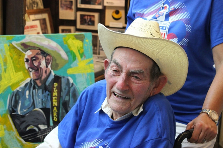 "In this July 2, 2017, photo Cajun musician D.L. Menard attends an event at the Acadian Museum in his home town of Erath, La., where a portrait, seen behind him, was presented as part of a tribute to the entertainer. Menard, whose song ""The Back Door"" is among the most popular in Cajun music, is dead at the age of 85. Louisiana Funeral Services and Crematory in Broussard said on its website that Menard died Thursday, July 27 at his home in Scott, Louisiana. (Janet McConnaughey via AP)"