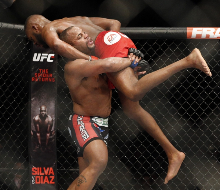 FILE - In this Jan. 3, 2015, file photo, Daniel Cormier, bottom, takes down Jon Jones during their light heavyweight title mixed martial arts bout at UFC 182 in Las Vegas. If Cormier wasn't Jones' bitter enemy, the UFC light heavyweight champion probably could could give sound advice to Jones, the troubled former champ. Instead, the steady Cormier realizes he needs a victory over his self-sabotaging archrival on Saturday, July 29, 2017, at UFC 214 to validate his own title reign. (AP Photo/John Locher, File)