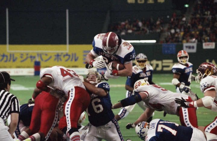 FILE - In this Jan. 12, 1992 file photo, East's Kevin Turner, of Alabama, dives over the top for a touchdown in the fourth quarter of the Japan Bowl, the American collegiate all-star football game, at the Tokyo Dome. A fullback at Alabama before playing eight years in the NFL for New England and Philadelphia, Kevin Turner was 46 when he died in 2016. He had been diagnosed with amyotrophic lateral sclerosis, known as ALS or Lou Gehrig's disease, but after studying his brain researchers declared that it was actually CTE. (AP Photo/Itsuo Inouye, File)