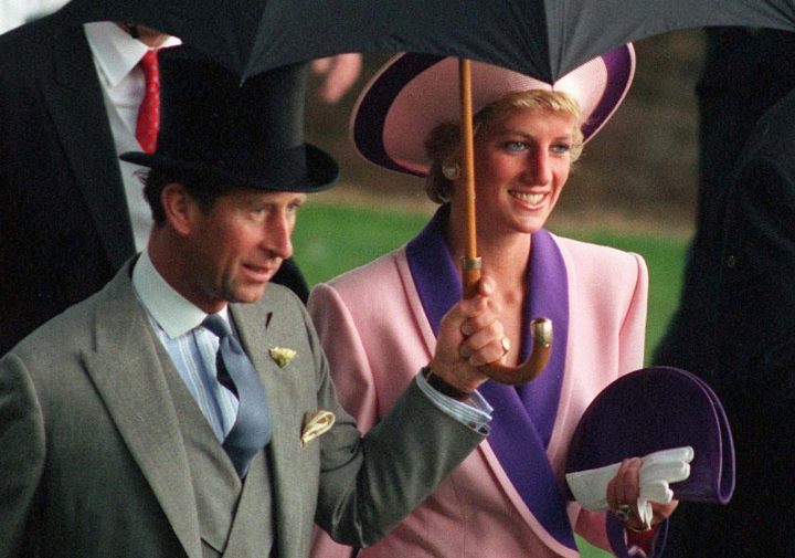 FILE- In this Wednesday, June 20, 1990 file photo, Britain's Princess Diana and Prince Charles, take shelter under an umbrella while attending the second day of the Royal Ascot horse race meet near London. A British television channel is broadcasting a new documentary on Princess Diana using video tapes in which she candidly discussed her marital problems and her strained relationship with the royal family. (AP Photo/Martyn Hayhow, File)