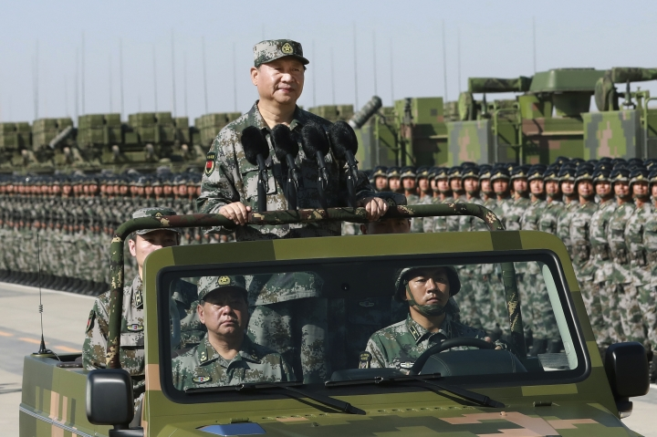 """In this photo released by Xinhua News Agency, Chinese President Xi Jinping stands on a military jeep as he inspects troops of the People's Liberation Army during a military parade to commemorate the 90th anniversary of the founding of the PLA at Zhurihe training base in north China's Inner Mongolia Autonomous Region, Sunday, July 30, 2017. China's military has the """"confidence and capability"""" to bolster the country's rise into a world power, President Xi Jinping said Sunday as he oversaw a large-scale military parade meant to show off the forces at his command to foreign and domestic audiences. (Li Gang/Xinhua via AP)"""