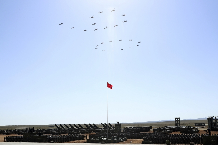 """In this photo released by China's Xinhua News Agency, Chinese army attack helicopters forming the number """"90"""" fly over a Chinese national flag Sunday, July 30, 2017 during a military parade to commemorate the 90th anniversary of the founding of the PLA on Aug. 1 at Zhurihe training base in north China's Inner Mongolia Autonomous Region. (Pang Xinglei/Xinhua via AP)"""