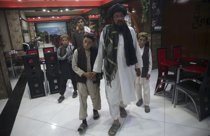 In this photo taken on Tuesday, July 25, 2017, Mohammed Naseer, with black turban, holds his sons' hand when they enter a Pizza Restaurant in Kabul, Afghanistan. Mohammed Naseer spent several weeks arranging for his son, a nephew and several other children from his district of Ander in Ghazni province to go to Quetta to study the Quran. (AP Photos/Massoud Hossaini)
