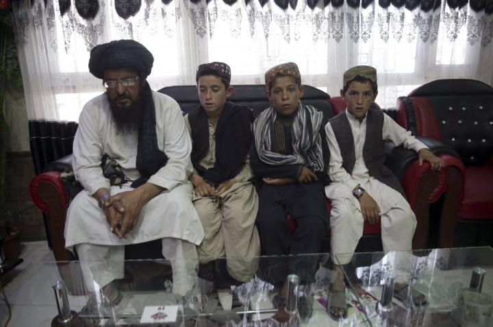 In this photo taken on Tuesday, July 25, 2017, Mohammed Naseer, with black turban, and three children wait for their food iN a Pizza Restaurant in Kabul, Afghanistan. Mohammed Naseer spent several weeks arranging for his son, a nephew and several other children from his district of Ander in Ghazni province to go to Quetta to study the Quran. (AP Photos/Massoud Hossaini)