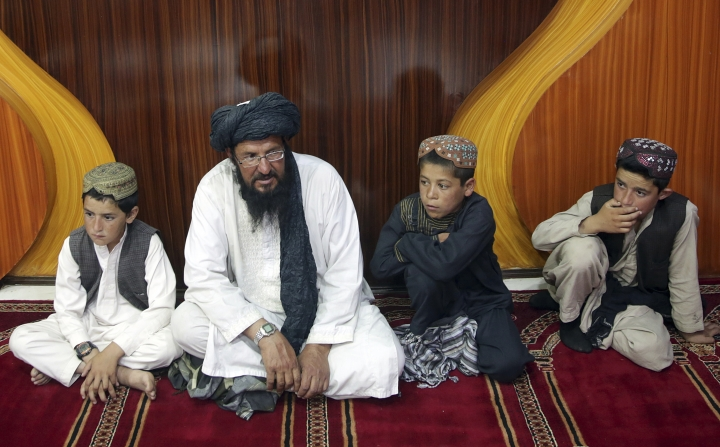 In this photo taken on Tuesday, July 25, 2017, Mohammed Naseer, with black turban, and three children wait for their food in the prayer area of a Pizza Restaurant in Kabul, Afghanistan. Mohammed Naseer spent several weeks arranging for his son, a nephew and several other children from his district of Ander in Ghazni province to go to Quetta to study the Quran. (AP Photos/Massoud Hossaini)