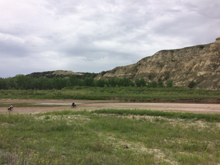 This June 20, 2017 photo shows Drew Redman and Ryan Johnson riding on the riverbed of the Little Missouri River in western North Dakota. The area is experiencing a drought this season, making it possible for Redman to ride across the low-flowing river. (AP Photo/Carey J. Williams)