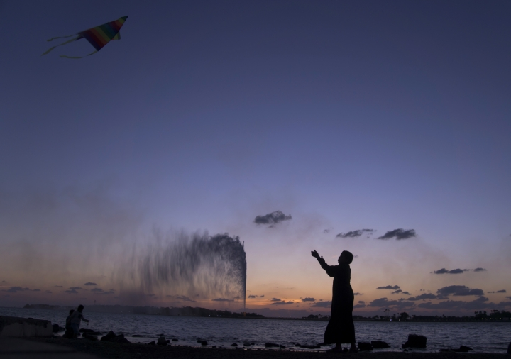 FILE- In this Monday, Feb. 20, 2017 file photo, a boy flies a kite on the Red Sea beach near the landmark Jiddah fountain, in Jiddah, Saudi Arabia. Saudi Arabia is planning to build a semi-autonomous luxury travel destination along its Red Sea coast that visitors can reach without a visa. The Red Sea area, which will include diving attractions and a nature reserve, will be developed with seed capital from the country's Public Investment Fund. (AP Photo/Amr Nabil, File)