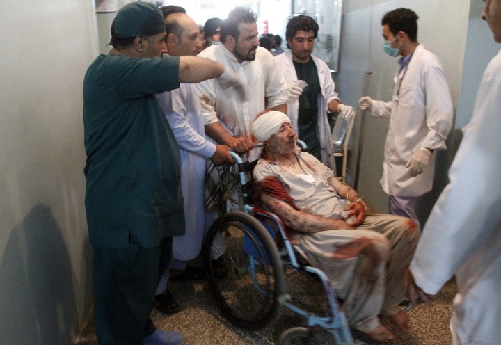 Relatives assist a wounded man in a hospital after a suicide attack on a mosque in Heart, Afghanistan, Tuesday, Aug. 1, 2017. An Afghan hospital official says an explosion inside a minority Shiite mosque in western Herat, on the border with Iran, has killed at least 20 people.(AP Photo/Hamed Sarfarazi)