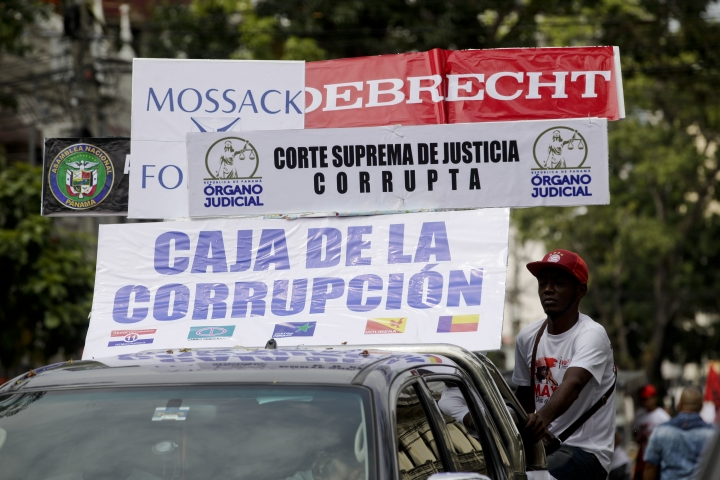 "FILE - In this May 1, 2017 file photo, banners on a car read in Spanish ""Corrupt Supreme Court"" and ""Corruption bank"" during the annual May Day parade in Panama City. Panama's Chief Prosecutor Kenia Porcell said Tuesday, Aug. 1, 2017 that the Brazilian construction company Odebrecht has agreed to pay Panama a $220 million fine and provide information about Panamanians who received bribes. (AP Photo/Arnulfo Franco, File)"