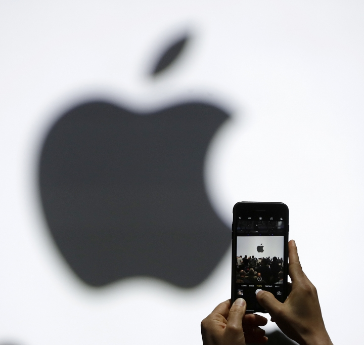FILE - In this Monday, June 5, 2017, file photo, a person takes a photo of an Apple logo before an announcement of new products at the Apple Worldwide Developers Conference in San Jose, Calif. Apple is getting ready to use iPhone cameras as an entryway into the strange world of augmented reality, taking the trend-setting company down an avenue that could usher in a new era in technology. (AP Photo/Marcio Jose Sanchez, File)