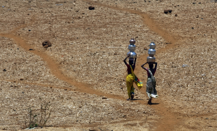 FILE- In this May 4, 2016 file photo, Indian women walk home after collecting drinking water from a well at Mengal Pada in Thane district in Maharashtra state, India. A new study suggests wide swaths of northern India, southern Pakistan and parts of Bangladesh may become so hot and humid by the end of the century it will be deadly just being outdoors. Such conditions would threaten up to a third of the 1.5 billion people living in those regions, unless the global community can rein in climate-warming carbon emissions. (AP Photo/Rajanish Kakade, File )