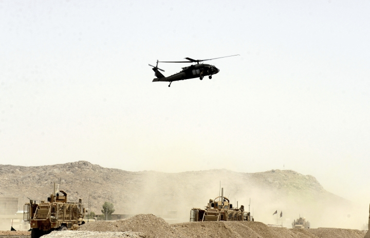 A US military helicopter flies over the site of a suicide bomb that struck a NATO convoy in Kandahar south of Kabul, Afghanistan, Wednesday, Aug. 2, 2017. A suicide bomber struck a NATO convoy near the southern Afghan city of Kandahar on Wednesday, causing casualties, the U.S. military said. (AP Photo)