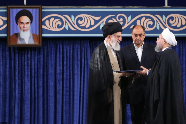 In this photo released by an official website of the office of the Iranian supreme leader, Supreme leader Ayatollah Ali Khamenei, left, gives his official seal of approval to President Hassan Rouhani as deputy chief of supreme leader's office Vahid Haghanian looks on in an endorsement ceremony in Tehran, Iran, Thursday, Aug. 3, 2017. A portrait of the late revolutionary founder Ayatollah Khomeini hangs at left. (Office of the Iranian Supreme Leader via AP)