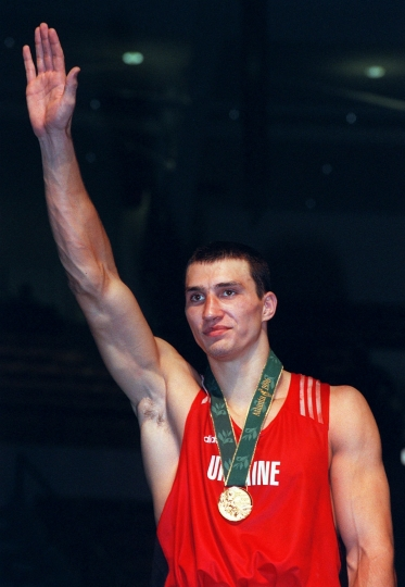 """FILE - In this April 8, 1996 file photo Ukrainian boxer Wladimir Klitschko poses with his gold medal at the 1996 Atlanta Olympic Games. Former heavyweight world champion Wladimir Klitschko has announced his retirement from boxing. In a statement released by his management Thursday, Aug. 3, 2017 Klitschko says: """"As an amateur and a professional boxer, I have achieved everything I dreamed of, and now I want to start my second career after sports."""" (AP Photo/Kathy Willens,file)"""