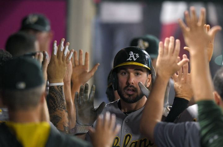 Oakland Athletics' Matt Joyce, center, is congratulated by teammates after scoring on a double by Khris Davis during the fifth inning of the team's baseball game against the Los Angeles Angels, Friday, Aug. 4, 2017, in Anaheim, Calif. (AP Photo/Mark J. Terrill)