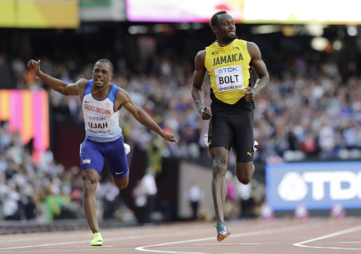 Jamaica's Usain Bolt, right, and Britain's Chijindu Ujah slow down after finishing a Men's 100m semifinal at the World Athletics Championships in London, Saturday, Aug. 5, 2017. (AP Photo/David J. Phillip)