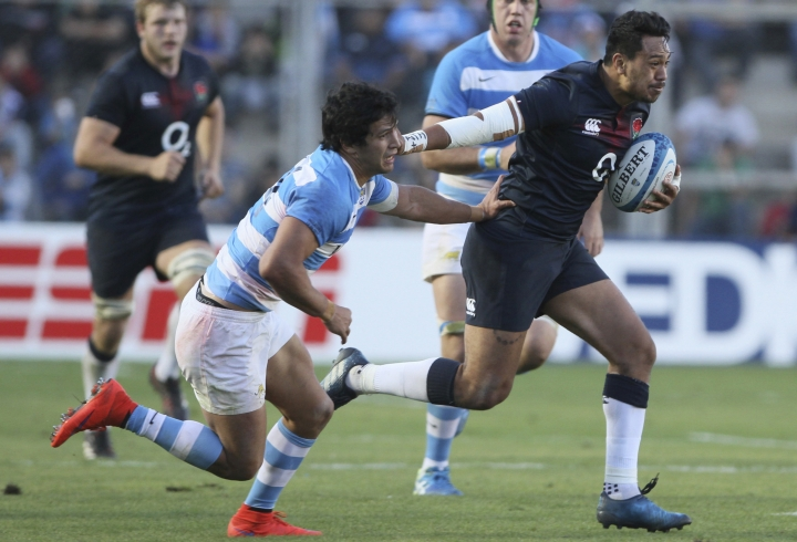 "FILE - This is a Saturday, June 10, 2017 file photo of England's Denny Solomona, right, runs as Argentina's Matias Moroni tries to stop him during a rugby test match in San Juan, Argentin. England's Rugby Football Union said Monday Aug. 7, 2017 that Denny Solomona and Manu Tuilagi have been sent home from a national team training camp. An RFU statement says the disciplinary action is a result of ""culture issues"" with no further explanation provided. (AP Photo/Emmanuel Rodriguez Villegas/File)"