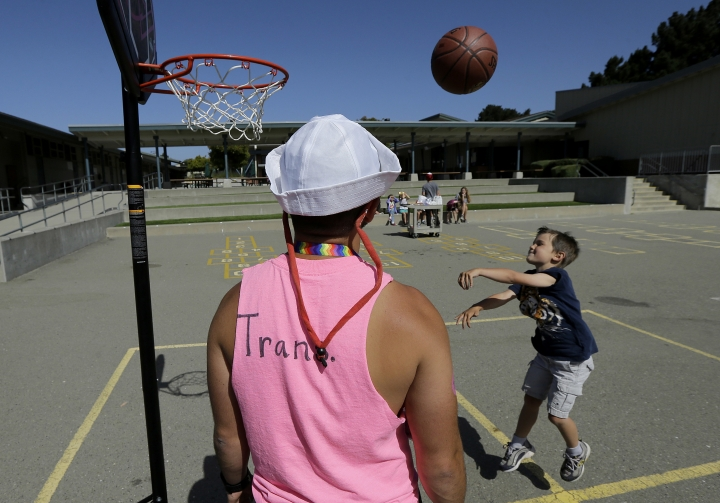 In this Tuesday, July 11, 2017 photo, camp instructor Kris Gambardella watches as camper Wilson shoots baskets at the Bay Area Rainbow Day Camp in El Cerrito, Calif., Tuesday, July 11, 2017. Gender experts say Rainbow's rapid growth reflects what they're seeing in gender clinics around the country: an increasing number of kids coming out as transgender at young ages. (AP Photo/Jeff Chiu)